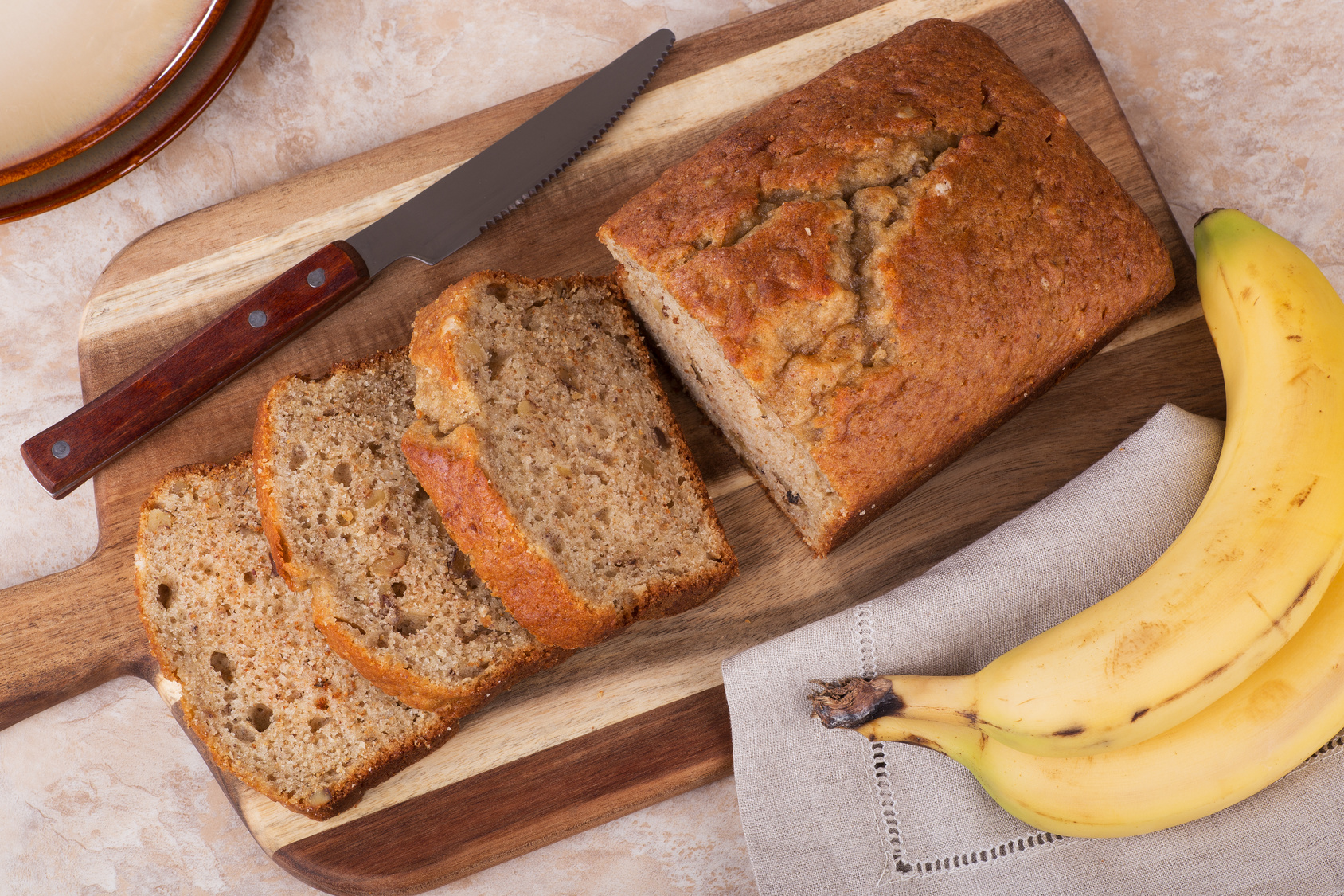 Banana nut bread sliced on a wooden cutting board with bananas on the side